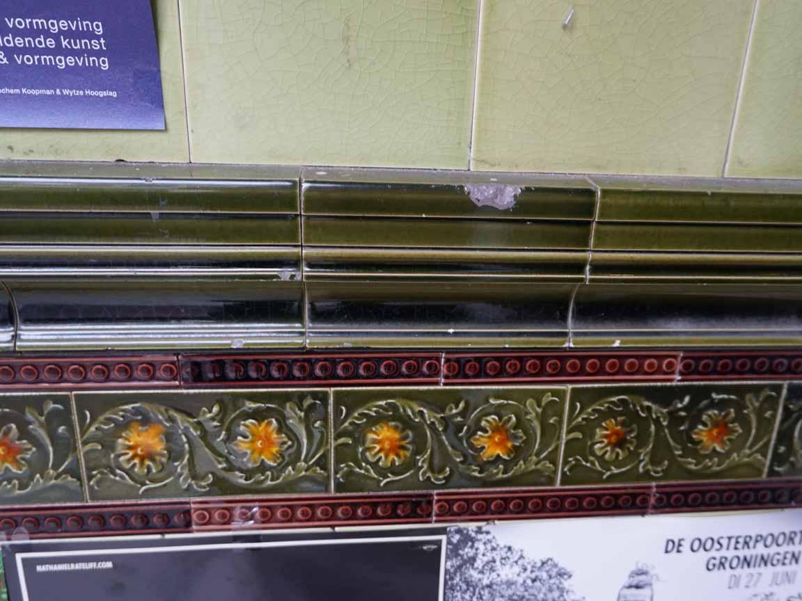 leicht beschädigte Jugendstil-Fliesen und florale Bordüren in der Kerkstraat in Assen / Niederlande