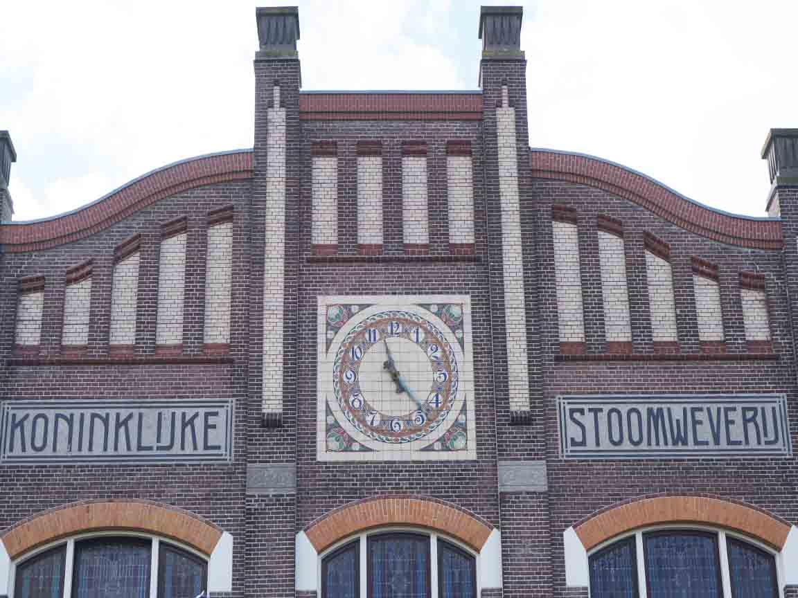 Fliesenbild mit Uhr an der Fassade einer Firma in Nijverdal / Niederlande