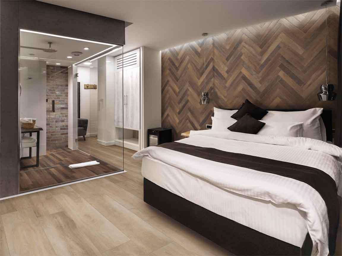 Keramisches Parkett auf dem Boden im Schlafzimmer und in der Dusche. An der Wand Fischgräte-Verlegung