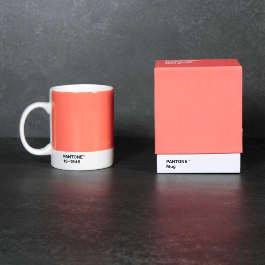 Pantone Tasse im Farbton Living Coral vor einem Feinsteinzeug in Metalloptik